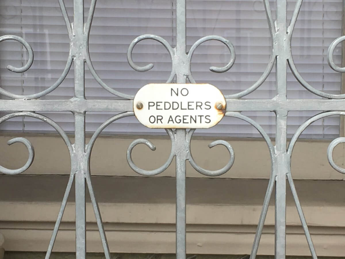 a gated door with a sign saying no peddlers or agents