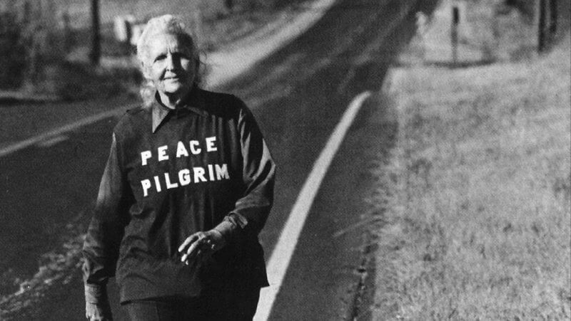 Peace Pilgrim walking, an older woman with white hair and a tunic that says Peace Pilgrim, she looks confident and happy and peaceful